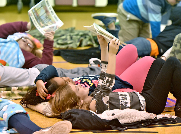 (Brad Davis/The Register-Herald) Crescent Elementary School students read together during the school's Read-a-Thon fundraiser Wednesday afternoon. The event was a different take on fundraising where every child got sponsors and collected donations in the hopes of raising a combined $5,000 towards playground equipment and other support items. Participating students then gathered Wednesday in the gym with a pillow and blanket to cozy up with as they read and were read to by their teachers.