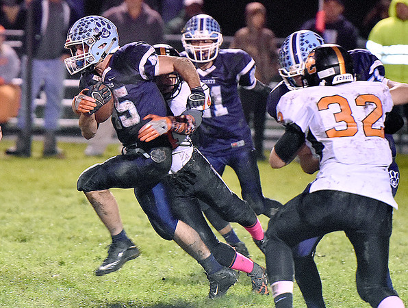 (Brad Davis/The Register-Herald) Meadow Bridge running back Caleb Richmond drags Summers County defender Christian Pack along for a few yards Friday night in Meadow Bridge.
