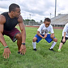 (Brad Davis/The Register-Herald) Former Flying Eagle and current Marshall University linebacker Chase Hancock, left, demonstrates the balance that comes from a proper two-point stance to young football players Jacob Buckland (right), 7, and Kingston Clark (left), 9, during the first ever Flying Eagles Fundamentals Camp Saturday Morning at Van Meter Stadium.
