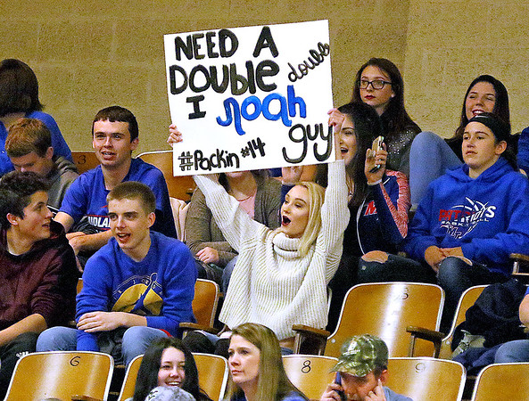 (Brad Davis/The Register-Herald) A visiting Midland Trail fan makes sure everyone knows where to find a double-double in Patriots basketball player Noah Minor (#14) with clever sign in support of him and the rest of the team during a road game at Fayetteville Friday night at the Soldiers & Sailors Memorial Building.