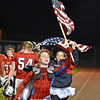 (Brad Davis/The Register-Herald) A pair of Indy students race up the track with American flags in celebration of a Patriot score Friday night in Coal City.