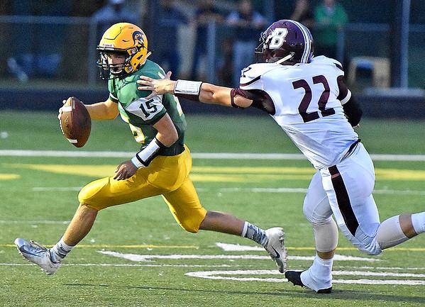 (Brad Davis/The Register-Herald) Greenbrier East quarterback Kyle King scrambles to avoid Woodrow Wilson defender Aiden Shehan August 31 in Fairlea.