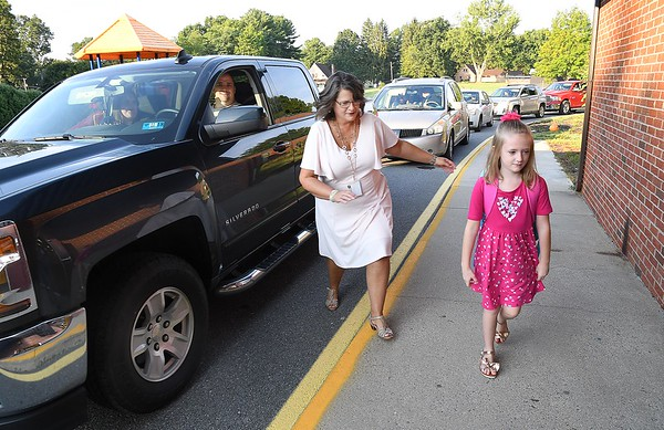 Crescent Elementary School Principal Theresa Lewis, left, guides Chole Yancey, first grader, inside the school during parent drop off for the first day of school in Raleigh County.<br /> (Rick Barbero/The Register-Herald)