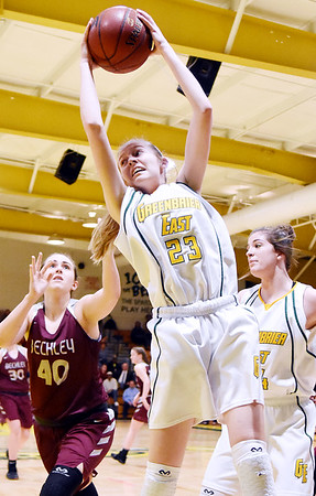 Greenbrier East's Haley McClure (23) grabs a rebound over Woodrow Wilson's Madison Miller (40) during the first half of their basketball sectional championship game in Lewisburg Friday. (Chris Jackson/The Register-Herald)