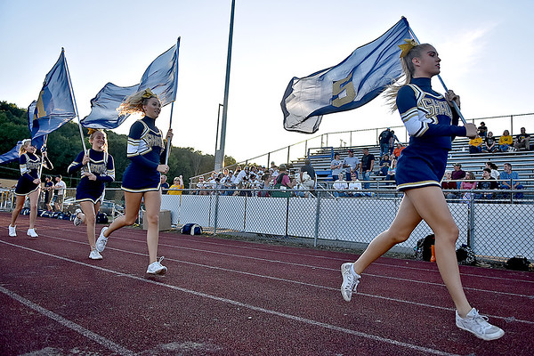 (Brad Davis/The Register-Herald) Shady Spring cheerleaders run with flags Thursday night in Shady Spring.