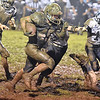 (Brad Davis/The Register-Herald) Meadow Bridge ball carrier Caleb Richmond trudges through the mud Friday night in Meadow Bridge.