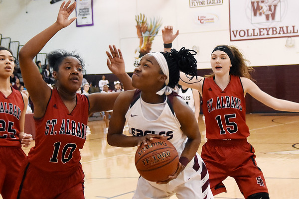 Woodrow Wilson's Sydni Darden (14) goes up for a shot over St. Alban's Aamiyah Washington (10) and Kamryn Hedrick (15) during the first half of their Class AAA, Region 3, conference final basketball game Tuesday in Beckley. (Chris Jackson/The Register-Herald)