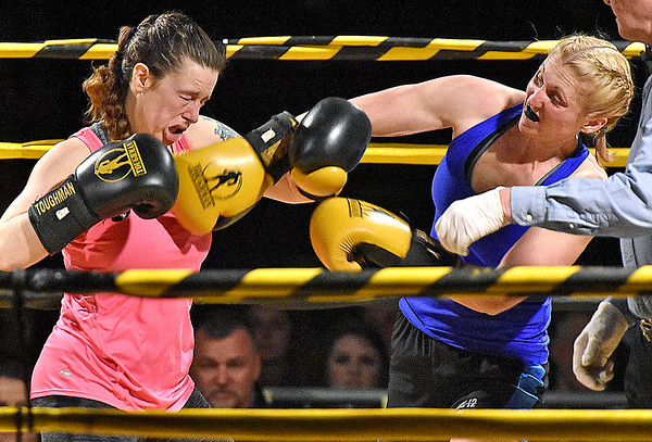 (Brad Davis/The Register-Herald) Sarah Coffey, right, catches opponent Candie Benedict with a right during their match in the Original Toughman Contest Friday night at the Beckley-Raleigh County Convention Center.