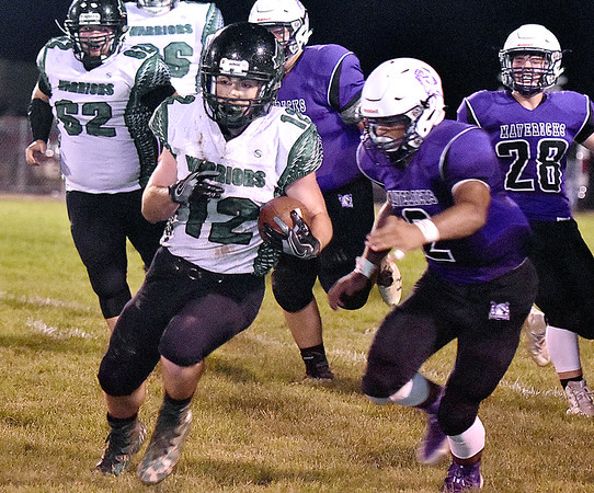 (Brad Davis/The Register-Herald) Wyoming East's Gage Bailey carries the ball as James Monroe defender Jaylon Lewis tries to run him down Friday night in Lindside.