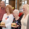 (Brad Davis/The Register-Herald) Longtime, retiring Plaza McDonald's employees Jessie Wolfe (45 years), middle right, and Mary Garris (40 years), each receive one of the two massive, hamburger cake toppers as they pose with owners Tim and Myra Harper at the conclusion of their retirement party September 19 at Black Knight.