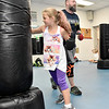 (Brad Davis/The Register-Herald) Eight-year-old Madalyne Phillips punches away as instructor Jamie Jesse monitor his class during the first Kids Combat Cardio session to be held Sunday afternoon at the YMCA of Southern West Virginia. The one hour class will be held every Sunday in two age groups, kids 5-10 at 3:00 p.m., kids 11-18 at 4:00 p.m. and combines a fun workout environment with basic mixed martial arts training and techniques.