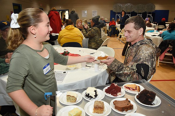 Laken Jarrell, left, serves dessert to Jim Ramsey, of Beckley during the Community Christmas Dinner held at The Place in Beckley Monday afternoon.<br /> (Rick Barbero/The Register-Herald)
