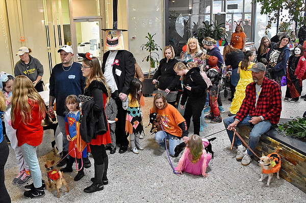 (Brad Davis/The Register-Herald) Costume-clad attendees wait patiently in line with their costume-clad pets to walk before the judges during the cotume contest portion of the Humane Society of Raleigh County's Howloween event Saturday afternoon inside the Beckley Plaza Mall.