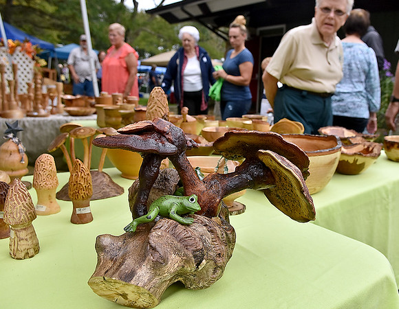 (Brad Davis/The Register-Herald) Guests pass by some interesting wood workings by Mills Mountain Crafters (Shoning and Judy Mills) as they browse wares from area artisans during the 31st Annual Cranberry Shindig Sunday afternoon at the Cranberry Nature Center in Hillsboro.