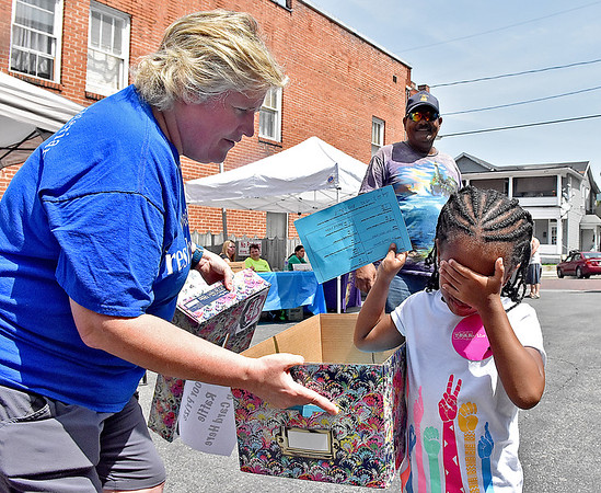 (Brad Davis/The Register-Herald) Six-year-old Zoe Lancaster covers hers eyes and draws a winner for one of several raffles as Terri Giles, one of the event organizers, holds the box during the Brothers & Sisters in Health event Thursday afternoon at First Presbyterian Church in Hinton. The event, sponsored by the church, Summers County ARH and West Virginians for Affordable Health Care, provided medical services to the public free of charge.