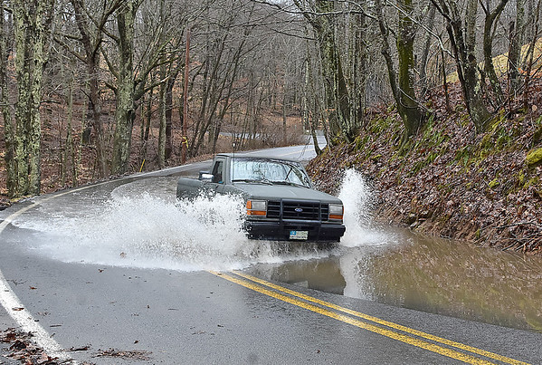 (Brad Davis/The Register-Herald) A motorist in a pickup truck makes their way through a deep pool of water left over from flooding along a section Odd Road near Ghent Sunday afternoon.
