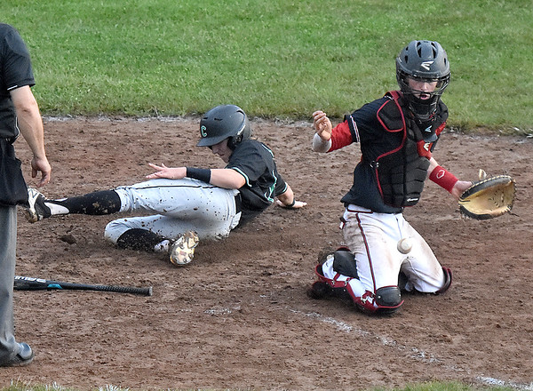 (Brad Davis/The Register-Herald) Charleston Catholic's Parker Ross slides and scores off teammate Thomas Blaydes' single as the throw to the plate gets away from Greater Beckley Christian's Brett Riffe to go up 9-8 in the top of the 7th inning Tuesday evening at Park Middle School.