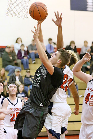 (Brad Davis/The Register-Herald) Wyoming East's Jacob Bishop drives and scores as Independence's Niko Burgess defends Friday night in Coal City.