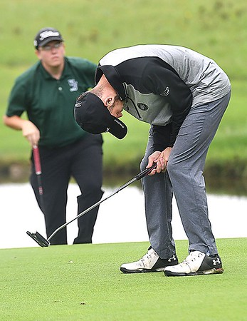 Michael Growe, of Wyoming East, left, watches Caleb Cook, of Wyoming East, react after just missing a putt on the par 5, 17th hole during the Class AA Region 3 golf tournament held at Grandview Country Club in Beaver.<br /> (Rick Barbero/The Register-Herald)