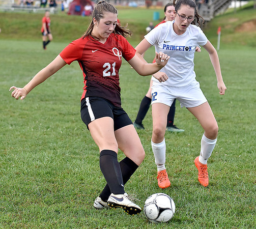 (Brad Davis/The Register-Herald) Oak Hill's Madison Wills works along the sideline as Princeton's Laken Dye rushes in to defend Thursday evening in Oak Hill.