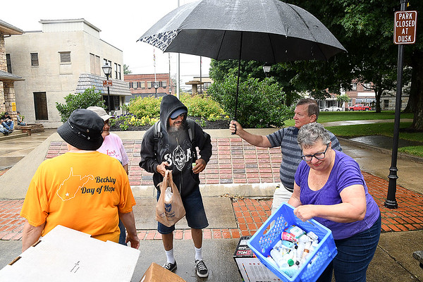 David Purch, currently living in a tent in Beckley, receives a free lunch from Calvary Assembly of God church members at Shoemaker Square in Beckley Tuesday afternoon. They set up every third and fifth tuesday from 11 am to 1 p.m. during the month and serve, hotdogs, sandwiches, chips, fruit snacks and water.<br /> (Rick Barbero/The Register-Herald)