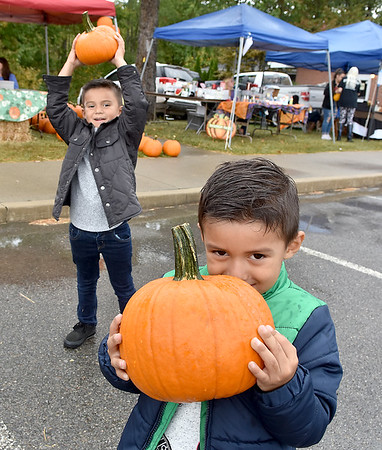 (Brad Davis/The Register-Herald) Four-year-old Giancarlo Solis, near, is a little shy while his older brother Matias, 5, is more than happy to show off his pumpkin as the two pick a couple of them out from the patch during Burlington United Methodist Family Services' annual Pumpkin Harvest Festival Sunday afternoon.