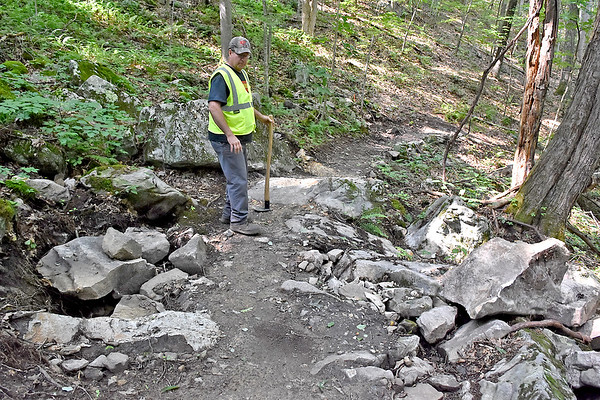 (Brad Davis/The Register-Herald) Gary Morefield, recently appointed as the City of Beckley's Trails Specialist, works on an area of new trails where he and other helpers have been sledgehammering out sections of rock to make them smoother for bikes around the YMCA Paul Cline Memorial Sports Complex Wednesday afternoon.