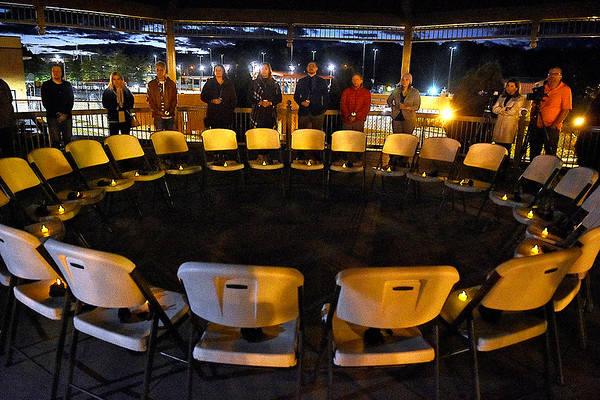 (Brad Davis/The Register-Herald) 24 empty seats sit empty with candles at each one underneath the Word Park gazebo in memory of the 24 lives lost statewide this year to domestic violence before the WRC's Candlelight Vigil gets underway Thursday night.