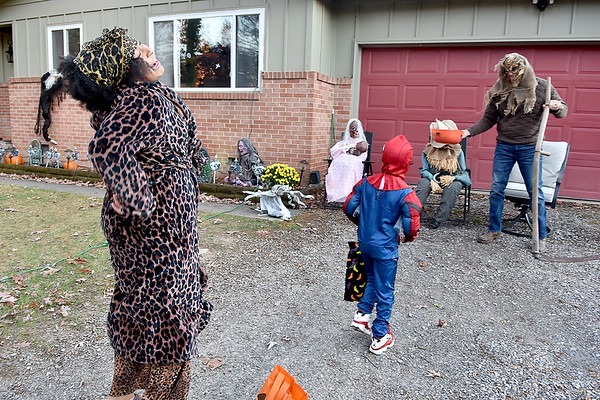 (Brad Davis/The Register-Herald) 10-year-old Aniya Lurch, left, jumps with laughter as she's startled by the ghoulish, automated props that suprise visitors upon approach to homeowner Derek Tilley's (right) well-decorated Crescent Road home Saturday evening. Five-year-old Carmelo Williams, middle, continues forward unphased.