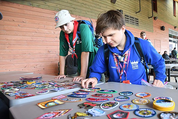 Boy Scouts Kai Leedy, of Bellingham, WA and Everett Hotter, of Potamac, MD, looking over patches to trade out during the World Scout Jamboree at the Summit Bechtel Reserve in Glen Jean.
