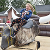 (Brad Davis/The Register-Herald) Harper Adkins, 5, hangs on as long as she can while going for a little rodeo action atop a bucking mechanical bull, one of a handful of activities going on during Burlington United Methodist Family Services' annual Pumpkin Harvest Festival Sunday afternoon. Adkins took three tries on the fun but difficult ride, staying on for a little longer each time.