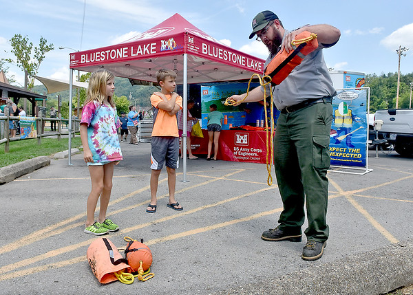 (Brad Davis/The Register-Herald) Army Corps of Engineers Park Ranger John Drossart teaches Glen Daniel residents Sara Canterbury, 8, and Gabe Acord, 10, how to use a rescue throw bag in the event they may need to help someone on the river one day, earning prizes while learning the technique in a target game format during the annual Safety On The Blue event Sunday afternoon at Hinton's Bellpoint Park. The event, put on every year by the Corps of Engineers along with the National Park Service, teaches kids of all ages how to stay safe on rivers, lakes and streams with games, a presentation on proper use of life jackets and how to determine their correct fit as well as a lifejacket giveaway.