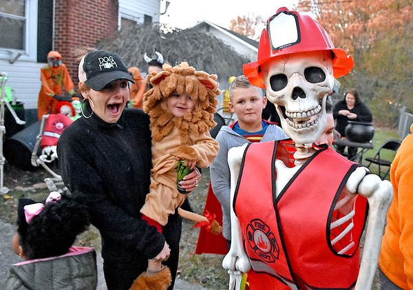 (Brad Davis/The Register-Herald) Young lion Andrew Gill, 2, isn't scared of a few skeletons residing in a spooky yard on Orchard Avenue as he smiles while being held by his aunt Felicia Smith, left, during Trick or Treating Saturday evening in Beckley.
