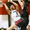 (Brad Davis/The Register-Herald) Greater Beckley Christian's Jay Moore powers his way to the basket for a layup as Trinity's Logo Zervos defends Saturday afternoon in Prosperity.