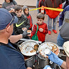 (Brad Davis/The Register-Herald) Dad Eric Lester, far right, looks on as kids Eli (middle in red), 7, and Parker (left of Eli), 10, gets cups of chicken chili from Lt. Rick Fisher (left handing chili) and Cpt. Joe Coughlin (lower right just out of frame) at the always-busy Beckley Fire Department booth during Chili Night festivities Saturday night in downtown Beckley.