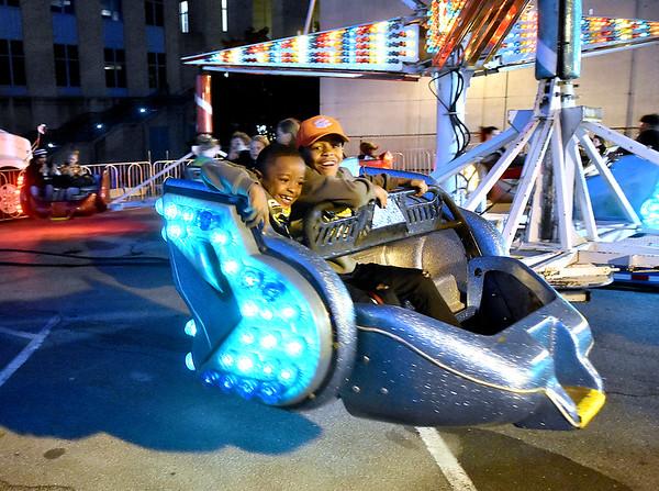 (Brad Davis/The Register-Herald) Kids ride the rides inside the carnival area Saturday night.