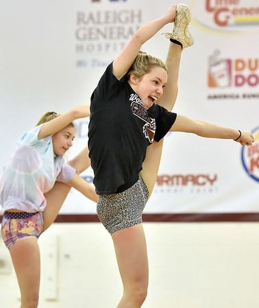 (Brad Davis/The Register-Herald) Woodrow Wilson cheerleaders Riley Pack, right, and Mattie Lewis stunt as they and teammates work through their freestyle routine in preparation for the upcoming state competition in Huntington during practice Wednesday afternoon.