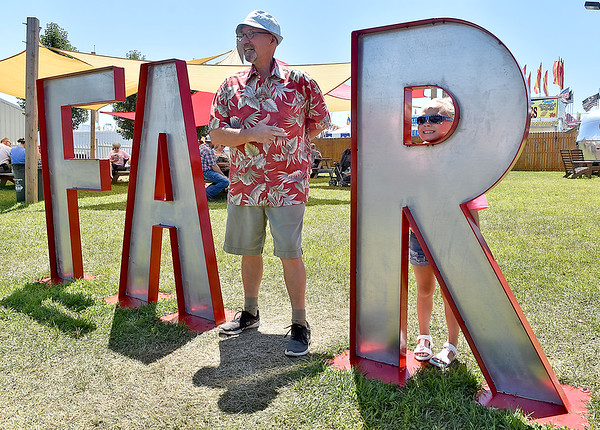 """(Brad Davis/The Register-Herald) Lewisburg resident Al Akers, playing the role of the """"I"""" in the FAIR sign, points over to his little cousin Riley Baisden as she peeks through the R Sunday afternoon at the State Fair in Fairlea."""