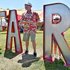 "(Brad Davis/The Register-Herald) Lewisburg resident Al Akers, playing the role of the ""I"" in the FAIR sign, points over to his little cousin Riley Baisden as she peeks through the R Sunday afternoon at the State Fair in Fairlea."