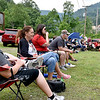(Brad Davis/The Register-Herald) Residents and family members take in the action as the Pirates play the Reds on the Big Coal River Little League's tee ball field Saturday afternoon in Pettus. Looming in the background at upper right is one of Contura Energy's mining operations, a company that for the last two years has had plans in the works on taking the property to install a belt line from that site down to another site that sits directly behind BCRLL fields. Though residents have known about the plans for some time, they now feel they were misled by Contura into thinking the company would replace their ballfields, which have been a staple in the community for the last 60 years.
