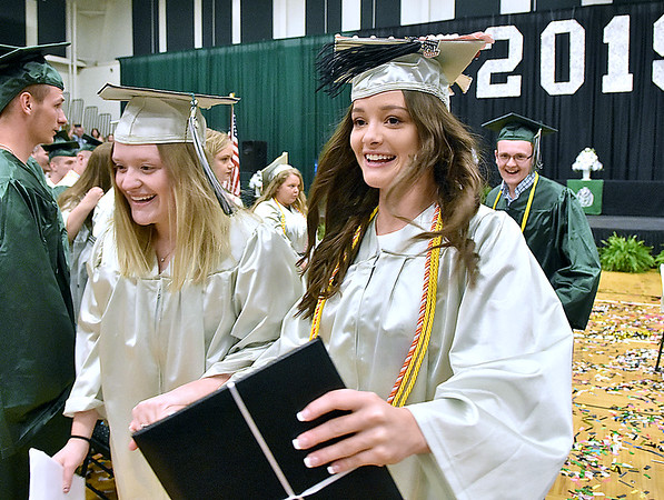 (Brad Davis/The Register-Herald) Wyoming East seniors Katie Daniels, right, and Morgan Cook exit the gym togather at the conclusion of the school's 2019 Commencement Ceremony Friday night in New Richmond.