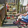(Brad Davis/The Register-Herald) Debbie Green describes the effort it used to take just to get up onto the front porch of her Harper Heights home as she watches a combined crew of volunteers from St. Luke Lutheran Church, St. Stephens Episcopal Church and the Mountain State Centers for Independent Living construct a wheelchair accessible ramp for her Sunday afternoon. Debbie has been mostly wheelchair-ridden with some use of a walker, and has had to be helped and/or carried up the stairs onto her porch by accompanying family for the last four years, making simple trips anywhere a huge undertaking. The family, like so many others who live with disabilities, are without adequate handicapped access at their homes with no means or ability to pay for or secure upgrades. Currently, a waiting list for federal funding for such facilities through MSCIL stretches four years and has 113 individuals on it in the state of West Virginia. St. Luke and St. Stephens, through their God's Work, Our Hands program, teamed up with Kelly Elkins at the Mountain State Centers for Independent Living to build a ramp for someone on their waiting list, and hopefully launch a potential longterm project that aims to bring in several other local churches to help provide the access ramps free of charge. It is Elkins' hope that this first project leads to more ramps for people in need who've waited so long, not just just locally but statewide.