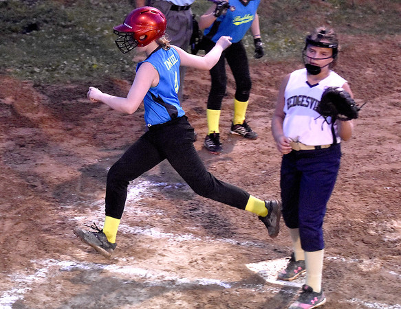 (Brad Davis/The Register-Herald) Beckley baserunner Beonca Daniel scurries home to score a run after a wild pitch from Hedgesville pitcher Chloe Frankhouser (covering the plate) during Little League 8-10 year-old Softball State Tournament action Wednesday night at Affinity park in Midway.