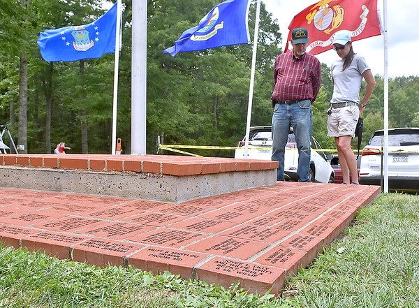 (Brad Davis/The Register-Herald) Shady Spring resident Melissa Lilly Griffith and uncle Charlie Lilly of Cool Ridge browse all the names that make up a growing memorial on the grounds of the Lilly Reunion Saturday.