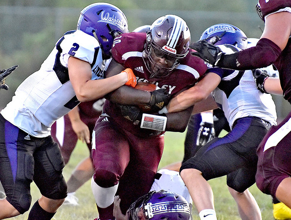 (Brad Davis/The Register-Herald) Woodrow Wilson's Lamont Lee drags Riverside defender Andrew Starcher, left, and a few other along with him as he carries the ball Friday night in Beckley.