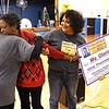 Ruth Catus, family friend, left and JoAnn Ross, sister, of late Reginald R. Rhodes, third from left, hugs Gloria Clark, pre-k teacher at Stratton Elementary School on South Kanawha Streret in Beckley, left, after she won the Reginald R. Rhodes Extraordinary Award. <br /> (Rick Barbero/The Register-Herald