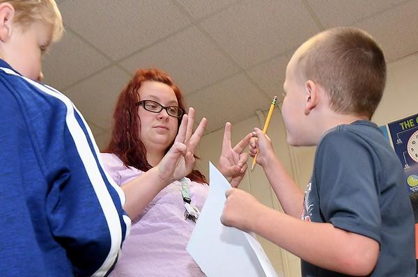 Crescent Elementary School first grade teacher Kayla Boyd helps Fenix Dayton slove a math problem.<br /> (Rick Barbero/The Register-Herald)