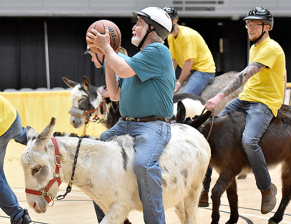 (Brad Davis/The Register-Herald) Butch Ragland gets his donkey in position for a shot as his team, the Jerusalem Cruisers, take on Buddy's Comancheros during a donkey basketball tournament to benefit the Raleigh County Horseman's Association Sunday afternoon at the Beckley-Raleigh County Convention Center. The rules are simple, as it's basically standard basketball, but you must be on your donkey when taking a shot. You can dismount to pick up a loose ball or move around the court quicker, but you must have your donkey in tow at all times when not riding it. RCHA hopes to have a few more of these events in the future.
