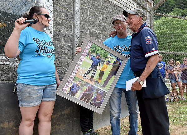 (Brad Davis/The Register-Herald) Big Coal River Little League's Marsha Evans, left, and Roger Clay, present a commemorative gift to umpire Jerry Jarrell, who's been at it for 53 years, during a homecoming ceremony at their complex in Pettus Saturday afternoon.