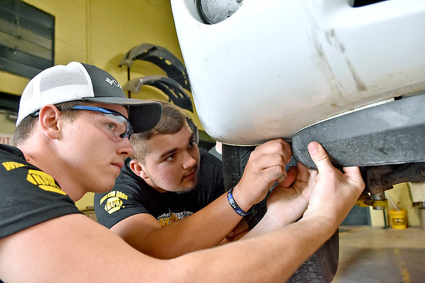 (Brad Davis/The Register-Herald) Greenbrier East juniors Austin Boone, left, and Tyler Boggs work on a vehicle inside the school's collision repair training center May 30 in Fairlea.